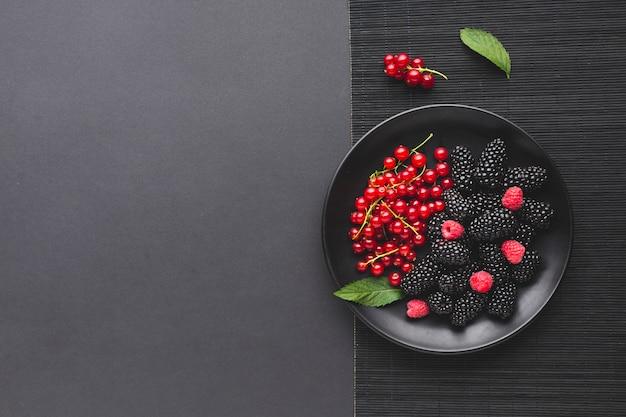 Плоская тарелка свежих ягод с copyspace