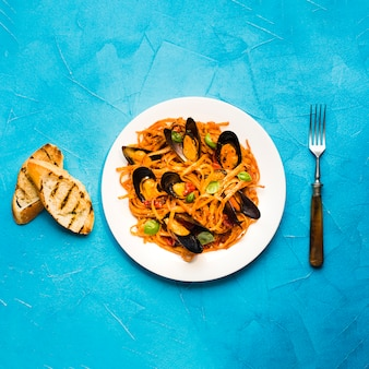 Flat-lay plate of pasta with mussels and fork