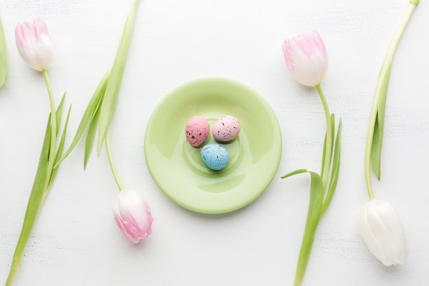 Flat lay of plate with colorful easter eggs and beautiful tulips