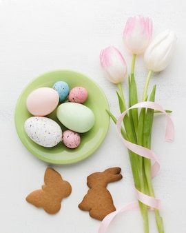 Flat lay of plate with colorful easter eggs and cookies