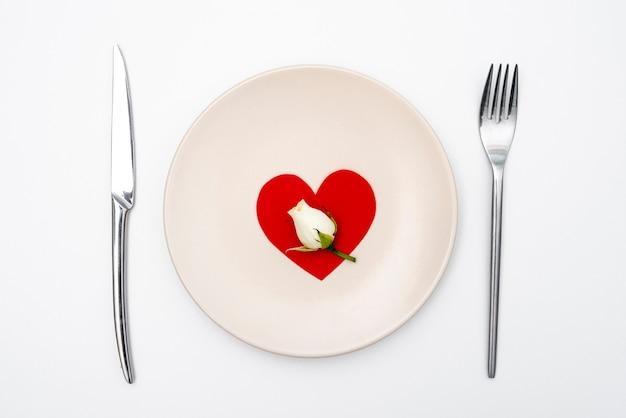 Flat lay of plate with heart and cutlery with rose