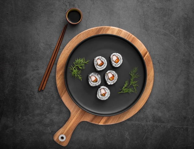 Flat lay plate with maki sushi and soy sauce