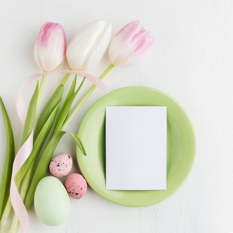 Flat lay of plate with piece of paper and tulips