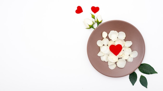 Flat lay of plate with rose petals and hearts