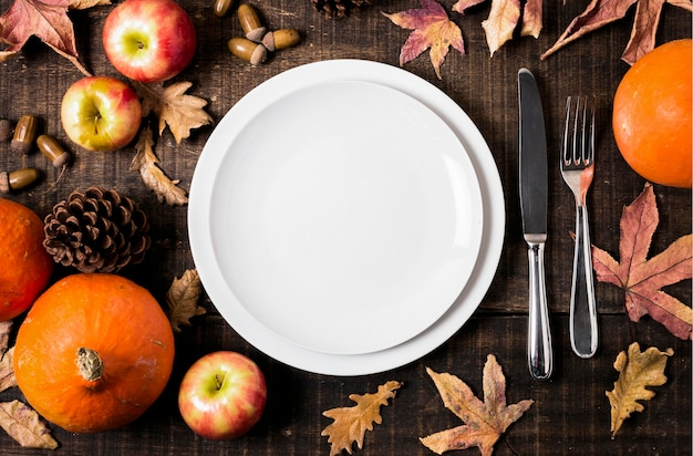 Flat lay of plates for thanksgiving dinner with autumn leaves