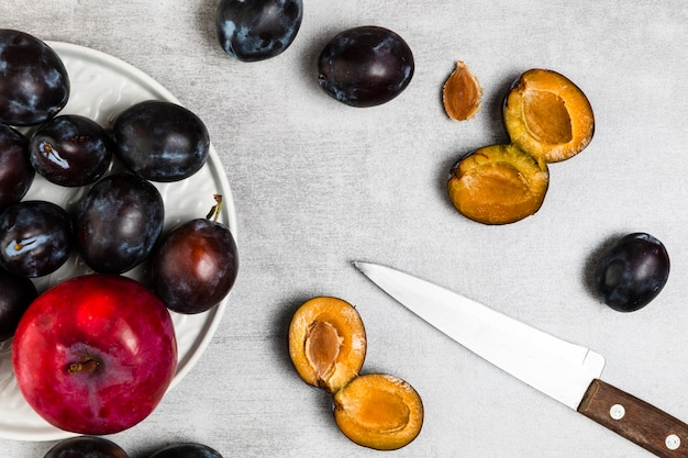 Flat lay of plums and apple on wooden background
