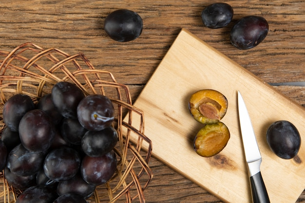 Flat lay of plums on chopper on wooden table