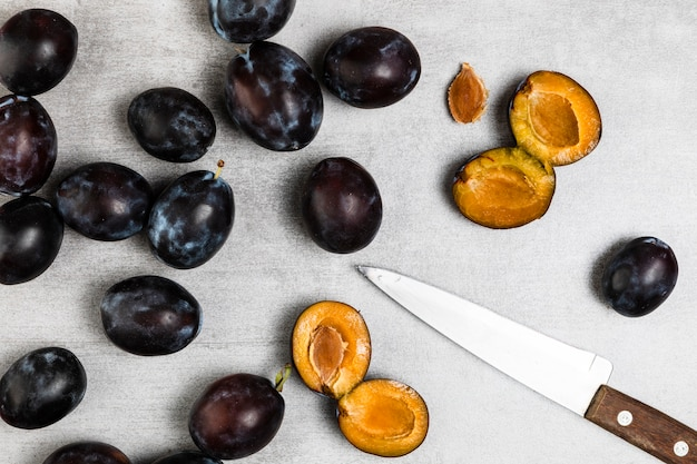 Flat lay of plums and knife on wooden background