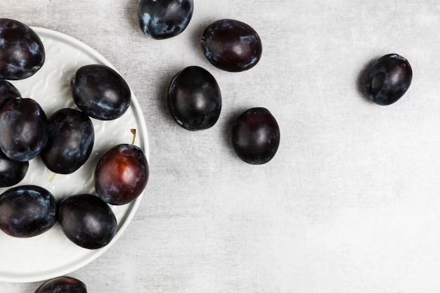 Flat lay of plums in plate on wooden background