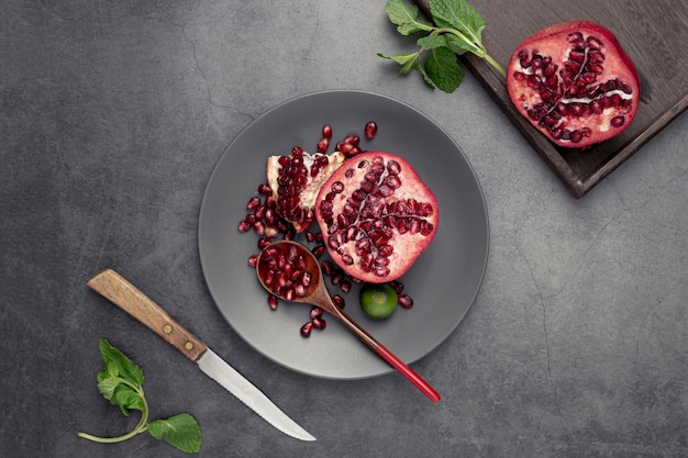 Flat lay of pomegranate on plate with mint and knife