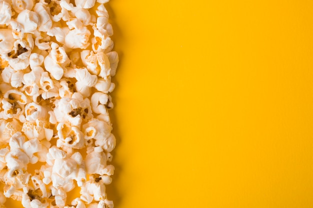 Flat lay popcorn on yellow background with copy space