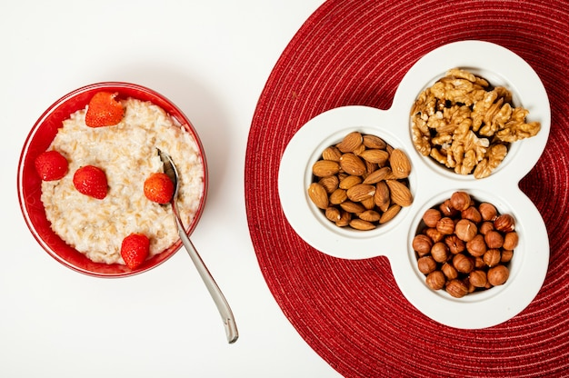 Flat lay porridge with nuts on plain background