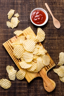Flat lay of potato chips with ketchup