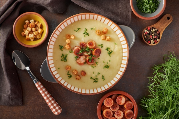 Flat lay of potato cream soup with croutons and sausage