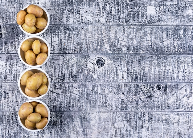Flat lay potatoes in bowls on gray wooden table