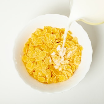 Flat lay pouring milk over the cornflakes