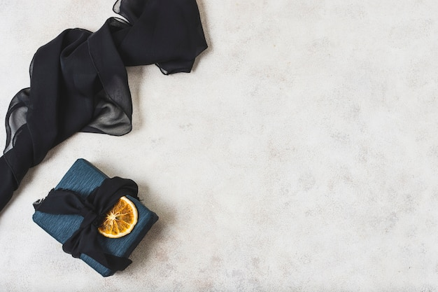 Flat lay of present with citrus slice and copy space