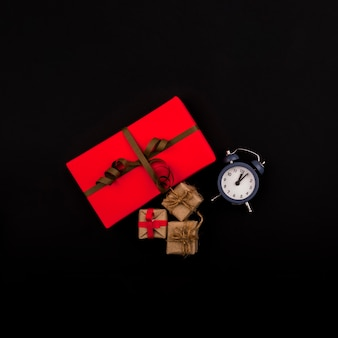 Flat lay of presents and clock on black background