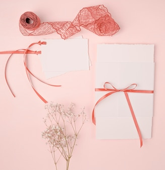 Flat lay pretty arrangement for wedding invitations on pink background