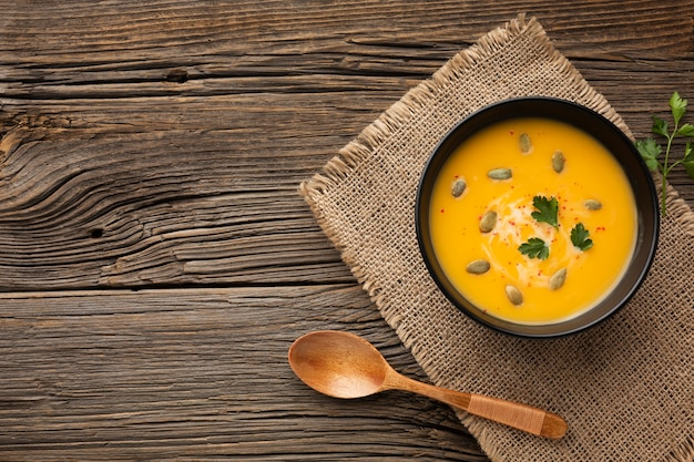 Flat lay pumpkin soup in bowl with copy space