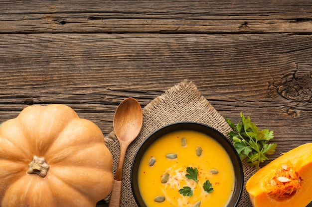 Flat lay pumpkin soup in bowl with pumpkin and copy space