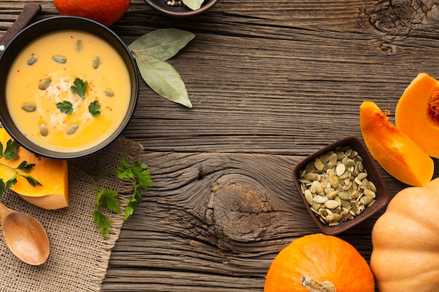 Flat lay pumpkin soup in bowl with pumpkin and wooden spoon and seeds