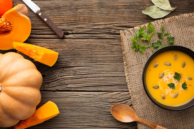 Flat lay pumpkin soup in bowl with pumpkin and wooden spoon