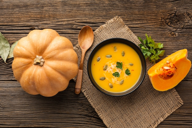 Flat lay pumpkin soup in bowl with pumpkin
