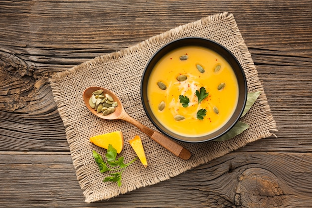 Flat lay pumpkin soup in bowl with wooden spoon