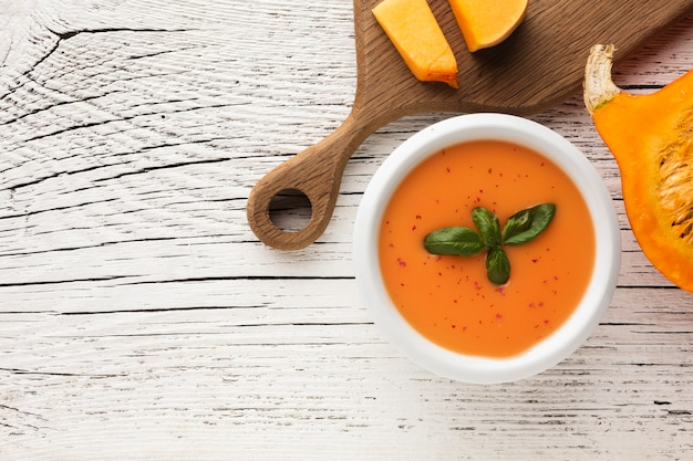 Flat lay pumpkin soup and pumpkin on cutting board with copy space