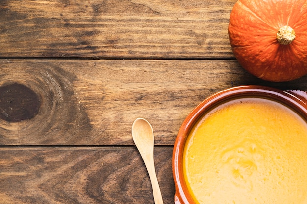 Flat lay pumpkin with soup and wooden spoon