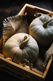 Flat lay pumpkins in a basket with burlap fabric