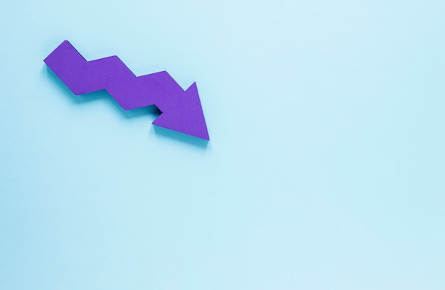 Flat lay purple arrow on blue background with copy-space