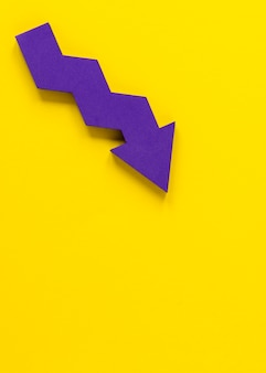 Flat lay purple arrow on yellow background with copy-space
