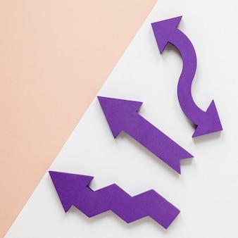 Плоские лежали фиолетовые стрелки и крем картон на белом фоне