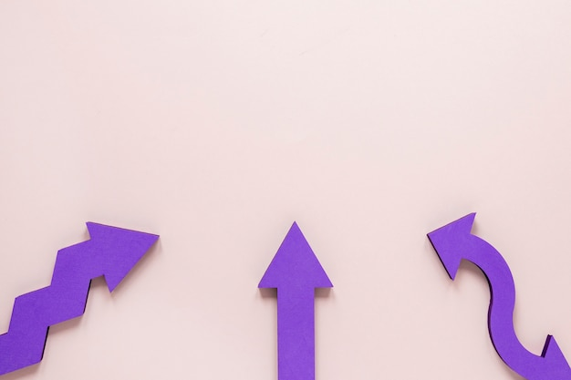 Flat lay purple arrows on pink background with copy-space