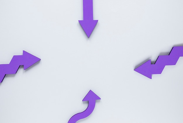 Flat lay purple arrows on white background