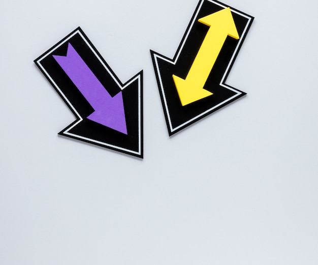 Flat lay purple and yellow arrows on white background