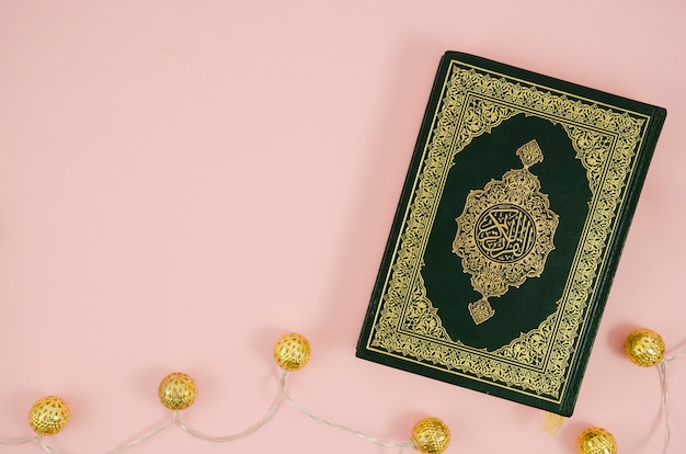 Flat lay quran on a light pink background