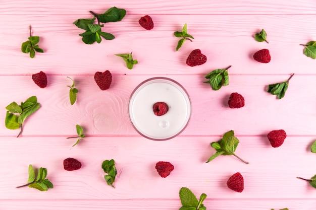 Flat lay raspberry milkshake on a pink wooden table