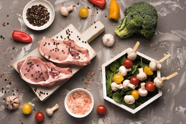 Плоский сырой стейк на деревянной доске с ингредиентами