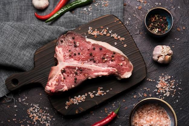Flat lay raw t-bone steak with pepper and salt