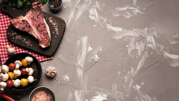 Flat lay raw t-bone steak with veggie skewers