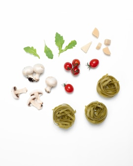 Flat lay of raw tomato pasta ingredients on white surface