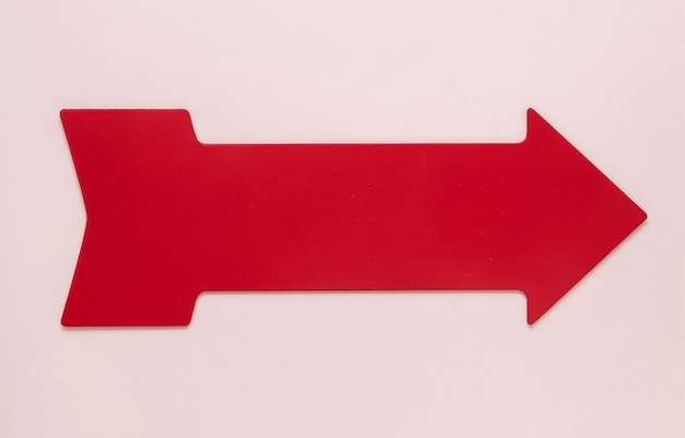 Flat lay red arrow on pink background