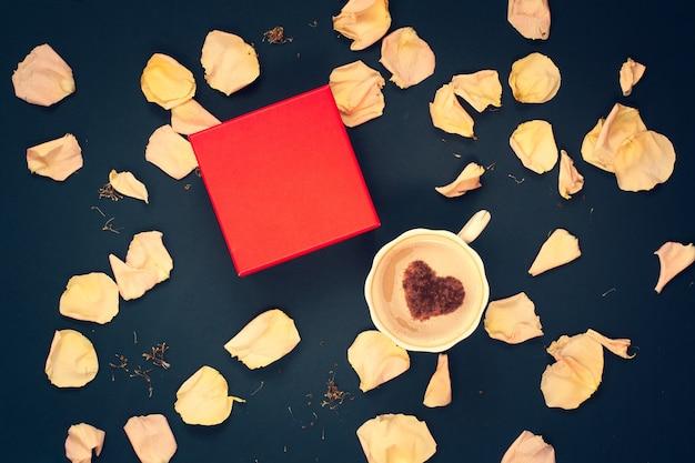 Плоская планировка. красная коробка, кофейная кружка со сливками и корицей в форме сердца с розовыми лепестками цветов на темно-синем фоне. скопируйте место на коробке для бренда. подходит для планировки. виньетирование.
