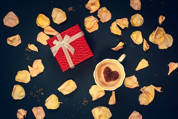 Flat lay. red box with a bow, a coffee mug with cream and cinnamon in the form of a heart with pink and yellow flower petals on a dark blue background.