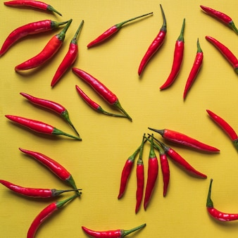Flat lay red chili peppers pattern on yellow background.