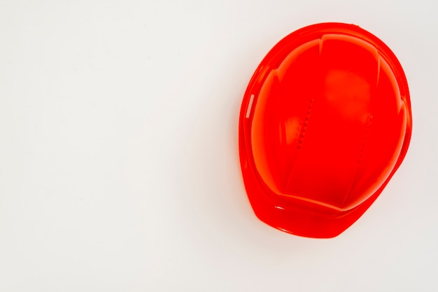 Flat-lay red construction helmet on white background