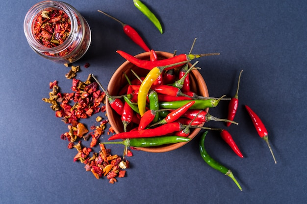 Flat lay red , green and yellow chili peppers in a bowl and paprica spice over gray background.
